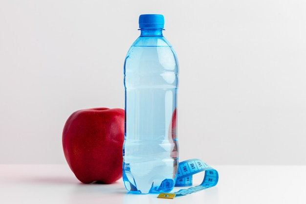 Bottle of water, measuring tape and fresh apple on the table