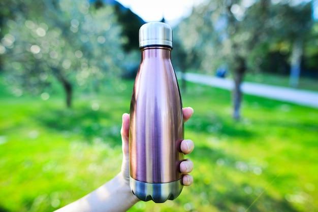 ボトルウォーター再利用可能女性の手でスチールエコサーモウォーターボトルのクローズアップ背景に再利用可能なアルミニウムボトルウォーター焦点が合っていないぼやけたエコフレンドリーウォーターボトルとオリーブの木の枝