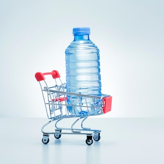 Bottle of water in shop trolley on gray surface. water delivery.