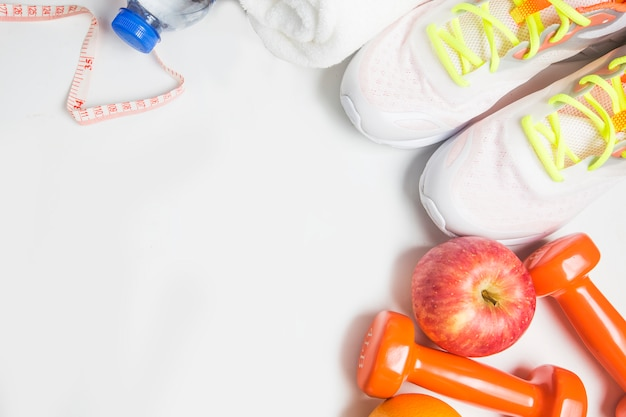 Bottle of water with sneakers and weights and an apple