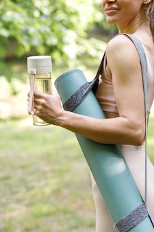 Bottle water and yoga mat in the hands of a woman in the park in the summer