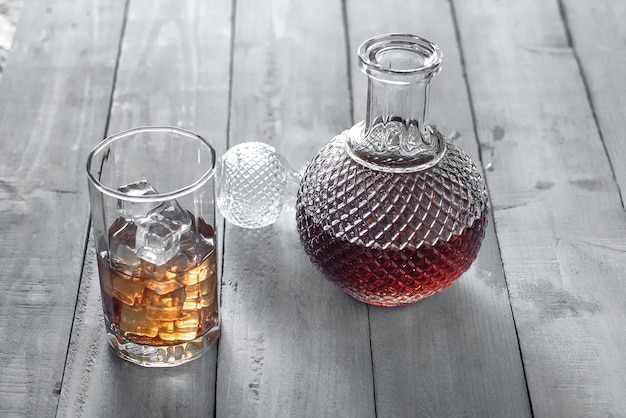 ボトルウィスキーと黒の背景に氷のウィスキーのガラス