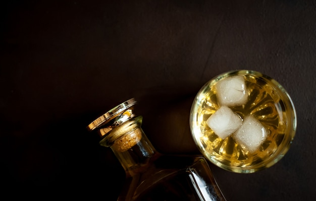 A bottle of whiskey and a glass of whiskey with ice on concrete