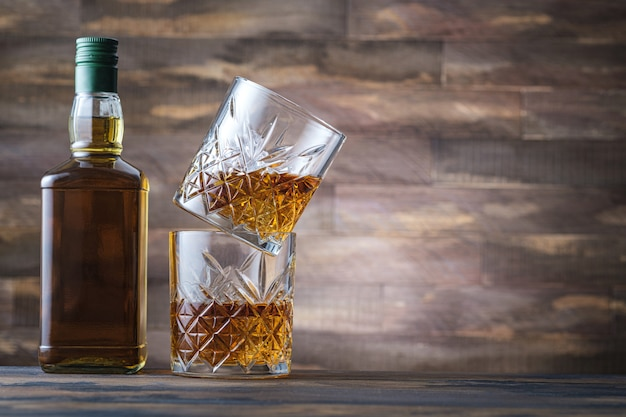 Bottle whiskey and two glass with bourbon or scotch