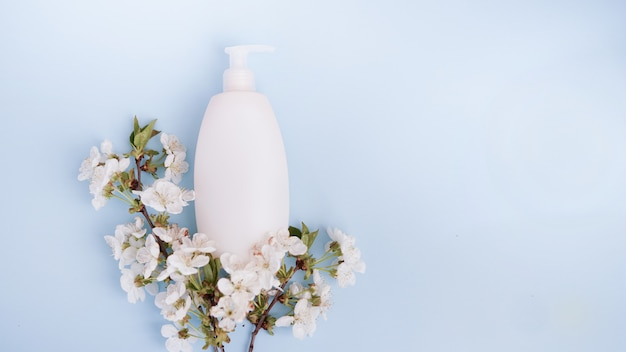 Bottle and white flowers on blue background.