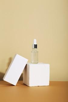 ベージュの背景と白いボックスにスポイトで白いガラスのボトル。スキンケアコンセプトのナチュラル化粧品