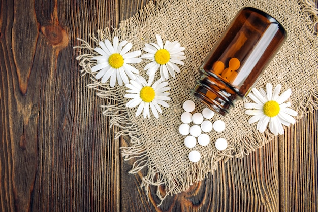 Bottle of white herbal pills and chamomile flowers on dark wood, homeopathic medicine.
