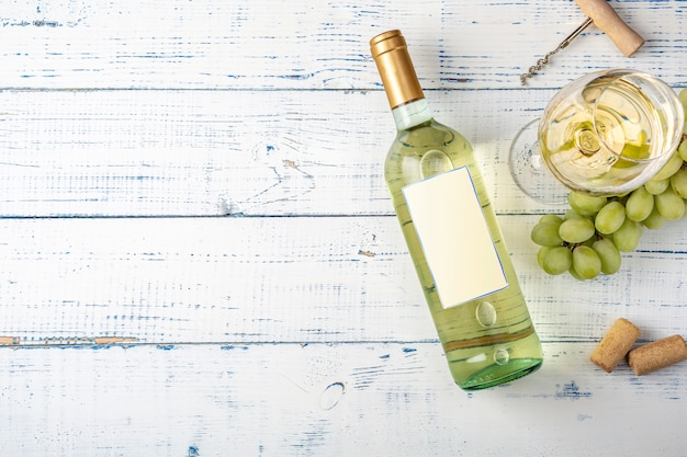 Bottle of white wine with label. glass of wine and grape. wine bottle mockup. top view.