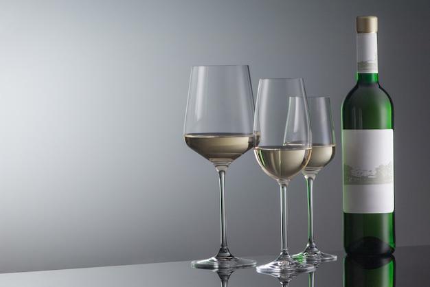 Bottle of white wine with wineglass on grey background with illumination