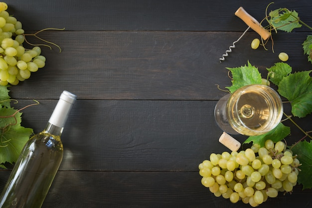 Bottle of white wine with wineglass, ripe grape on black wooden table.