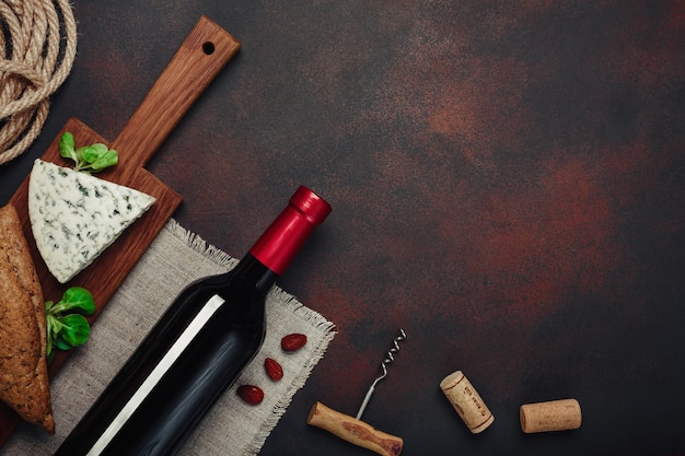 Bottle of wine, almonds, corkscrew and corks, on rusty background top view