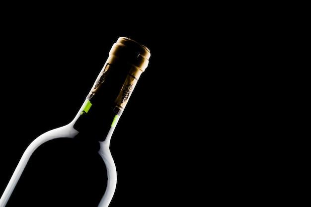 Bottle of wine over black wall