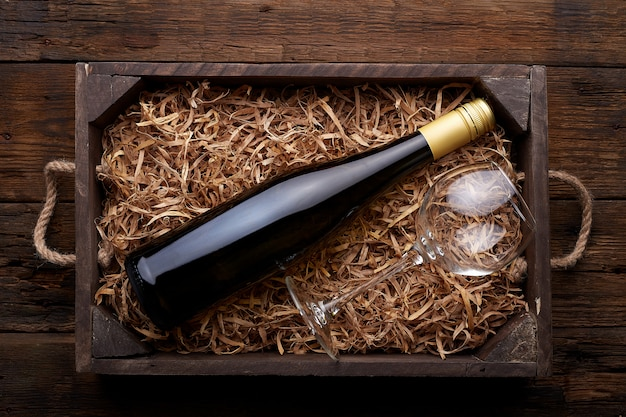 Bottle of wine in case on rustic wood