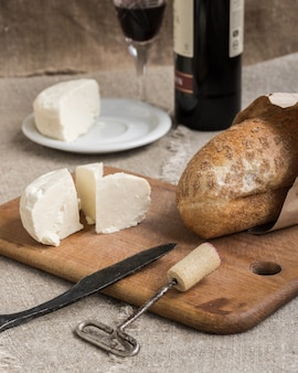 Bottle of wine, cheese and bread are on sacking