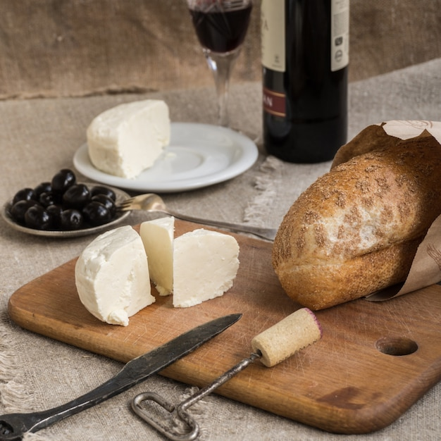 Bottle of wine, cheese and white bread are on sacking