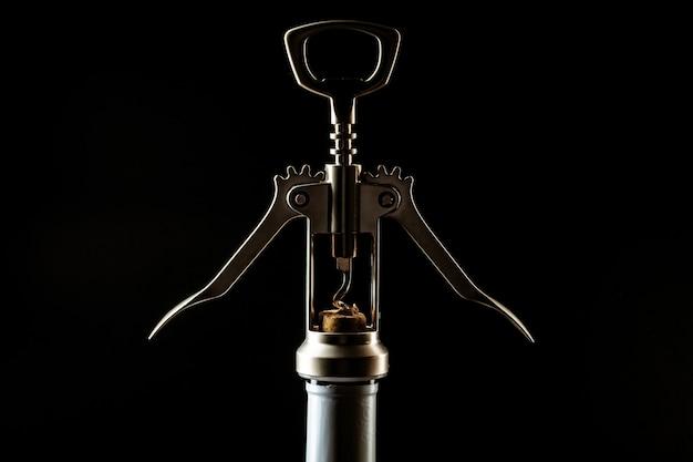 Bottle of wine and corkscrew over dark