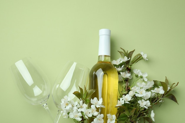 Bottle of wine, glasses and flowers on green background