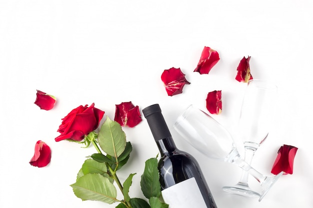 Bottle of wine, glasses and red roses