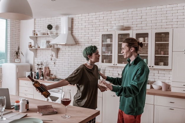 Bottle of wine. green-haired wife addicted to alcohol holding bottle of wine after drinking on her own