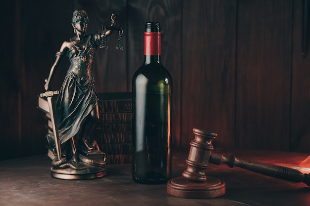Bottle of wine and lady of justice and judge gavel as a symbol of law on a wooden table