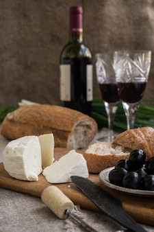 Bottle of wine, olives, cheese and bread are on sacking