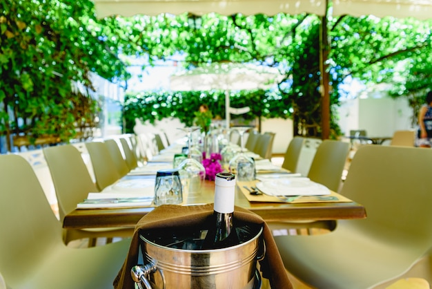 Bottle of wine opened in a bucket to cool it, in a mediterranean restaurant with vineyards.