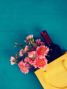 Bottle of wine in the package with a gift, flowers, on wooden background, copy space, gift, holiday,