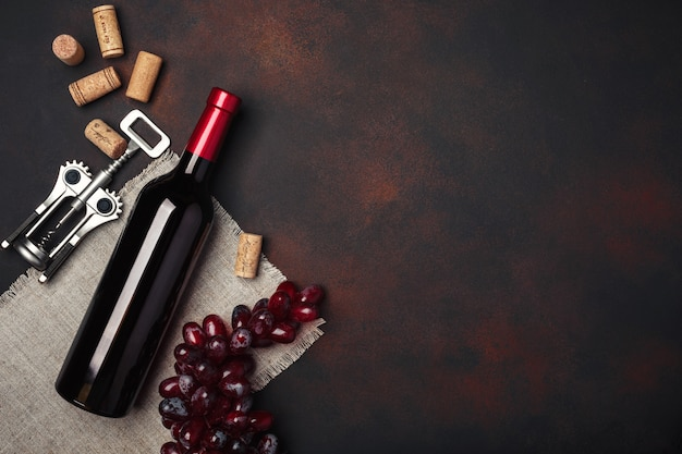 Bottle of wine, red grapes, corkscrew and corks, on rusty background top view