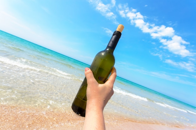 Bottle of wine in sand on the beach
