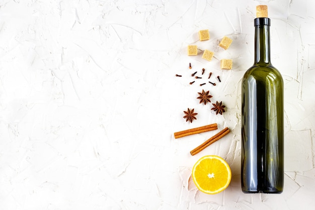 Bottle of wine and spice on white background. ingredients for a mulled wine. cinnamon, anise stars, orange, brown sugar, cloves. christmas hot drink