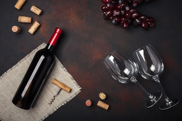 Bottle of wine, two glasses, corkscrew and corks, on rusty background top view, copy space