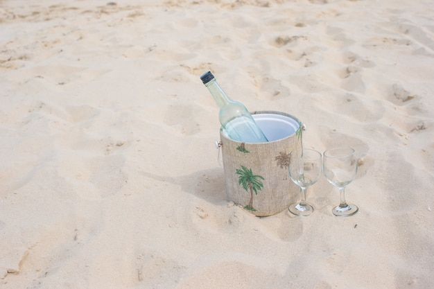 Bottle of wine and two glasses on sandy beach