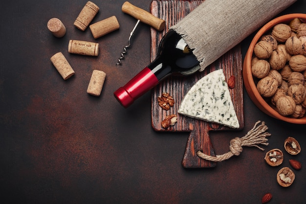 Bottle of wine, walnut, blue cheese, almonds, corkscrew and corks, on rusty background top view