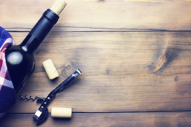 Bottle of wine with corkscrew isolated on wooden table