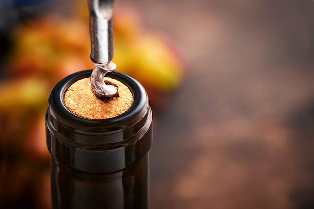 コルク栓抜きのボトルワイン。レストランで栓抜きでワインボトルを開ける。コピースペースのある暗い素朴な背景のワイン組成。モックアップ。