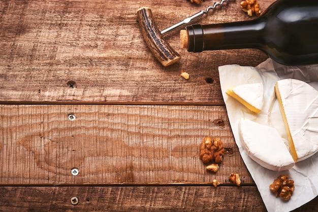 コルク栓抜きのボトルワイン。ブドウ、スライスチーズカマンベール、コピースペースのある古い灰色のコンクリートテーブルの背景にナッツ。つるの枝を持つ赤ワイン。素朴な背景のワイン組成。モックアップ。