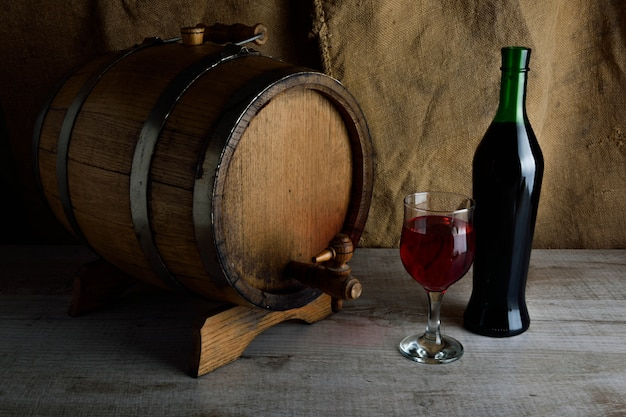 Bottle of wine with a glass and a corkscrew on a wooden background