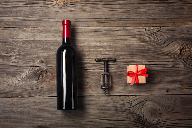 Bottle of wine with wine glass and gift box on wooden background. top view with copy space for your text.