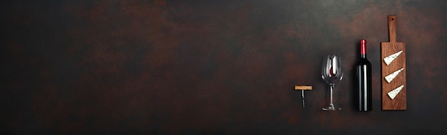 Bottle of wine with wineglass and gift box on rusty brown background. panoramic top view with copy space for your text.