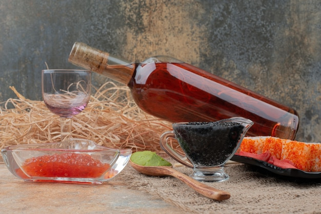 Bottle of wine with wineglass and sushi on burlap