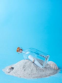Бутылка с сообщением на песке с синим фоном