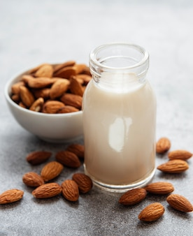 Bottle with almond milk and almonds on the table