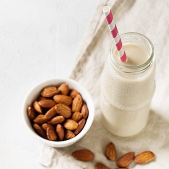Bottle with almonds milk and some almonds on white background