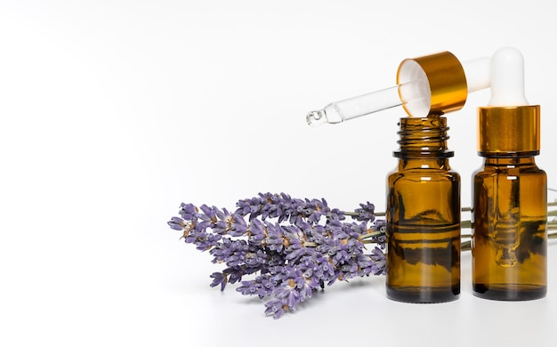 Bottle with aroma oil and lavender flowers on white background.