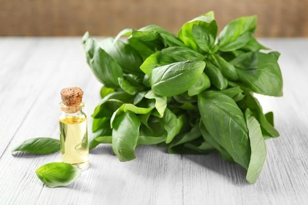 Бутылка с базиликовым маслом и зелеными листьями на деревянном столе