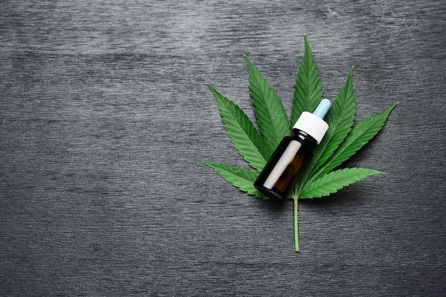 A bottle with cbd cannabis or hemp oil on the leaf of marijuana on the black wooden background with copy space. alternative medicine concept. cosmetics and skin care products.
