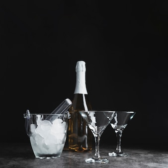 Bottle with champagne glasses and ice