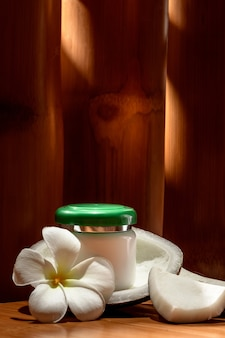 Бутылка с косметическим кремом на фоне кокоса и цветка плюмерии.