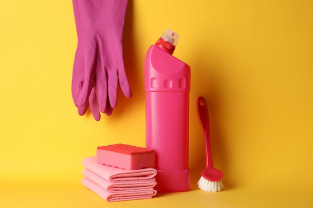 Bottle with detergent and cleaning supplies on yellow background, space for text