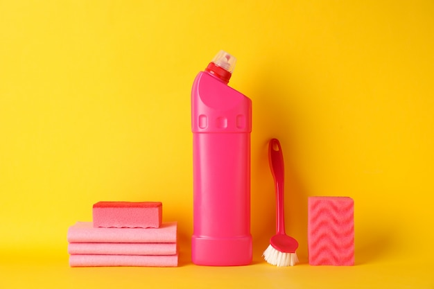 Bottle with detergent and cleaning supplies on yellow, space for text